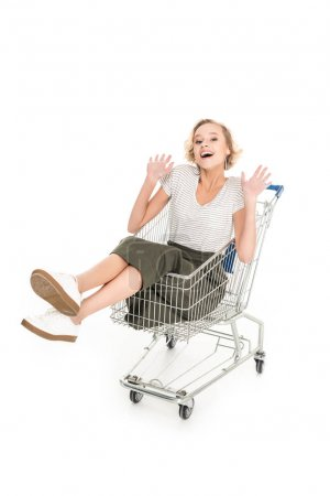 cheerful young woman sitting in shopping trolley and smiling at camera isolated on white