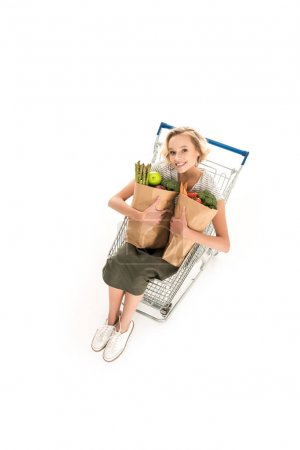 high angle view of girl smiling at camera while holding grocery bags and sitting in shopping trolley isolated on white