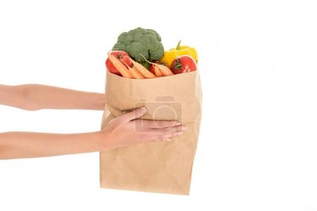 close-up partial view of woman holding paper bag with fruits and vegetables isolated on white