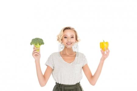 beautiful young woman holding fresh broccoli with pepper and smiling at camera isolated on white