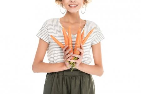 cropped shot of smiling young woman holding ripe carrots isolated on white