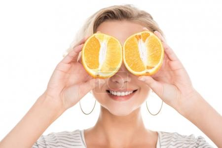 beautiful smiling young woman holding halves of orange near face isolated on white