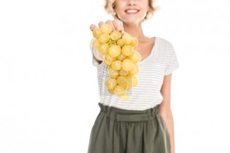 close-up partial view of smiling young woman holding fresh ripe grapes isolated on white