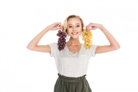 beautiful young woman holding bunches of grapes and smiling at camera isolated on white