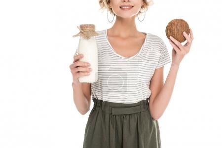 partial view of smiling woman holding coconut and coconut milk in hands isolated on white