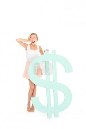 excited young woman with eyes closed standing at dollar sign isolated on white