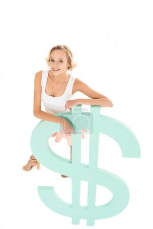 high angle view of smiling woman leaning on dollar sign and looking at camera isolated on white