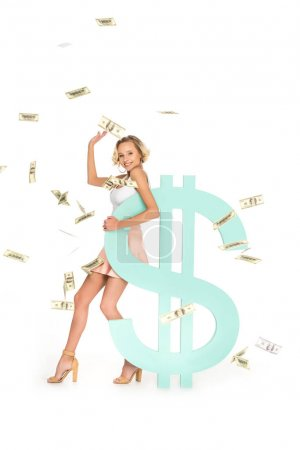 smiling young woman leaning on dollar sign with falling dollars around isolated on white
