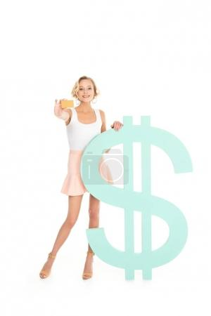 smiling woman showing credit card in hand while standing near dollar sign isolated on white