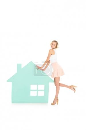 young smiling woman standing near house model isolated on white