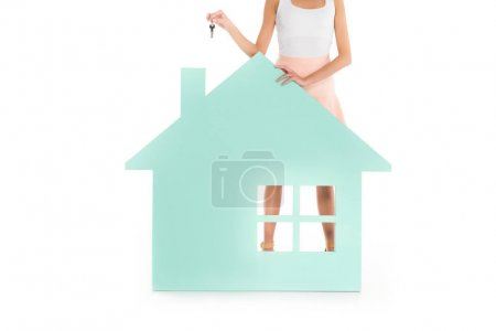 Photo for Partial view of woman with keys in hands standing at house model isolated on white - Royalty Free Image