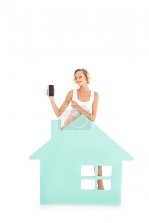young woman pointing at smartphone in hand while standing near house model isolated on white