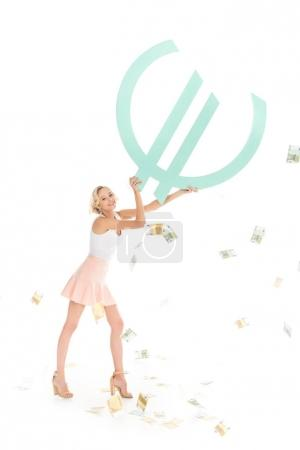 smiling young woman holding big euro sign with falling cash around isolated on white
