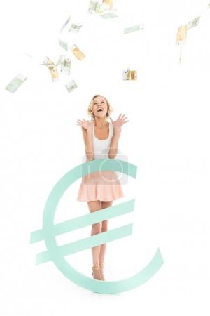 excited woman looking at falling cash while standing at euro sign isolated on white