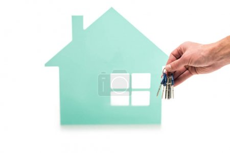 cropped shot of male hand with keys and house model isolated on white