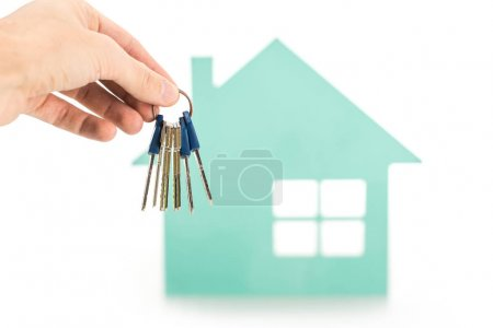 Photo for Cropped shot of male hand with keys and house model isolated on white - Royalty Free Image