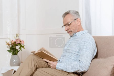Photo for Senior man reading book on sofa in cozy room - Royalty Free Image