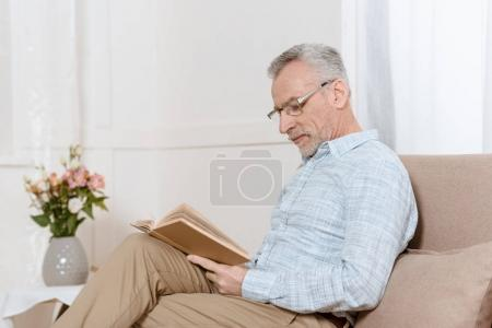 Senior man reading book on sofa in cozy room