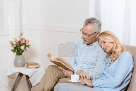 Mature man reading book on sofa while woman is asleep on his shoulder