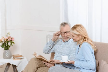 Middle aged woman and man reading book together on sofa in light room
