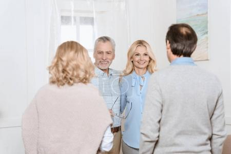 Couple of middle aged man and woman greeting their friends as guests