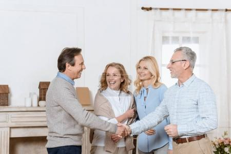 Senior man and woman greeting their friends as guests and shaking hands