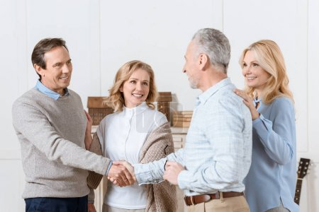 Photo for Couple of middle aged man and woman greeting their friends as guests and shaking hands - Royalty Free Image