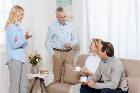 Senior men and women having a conversation while drinking tea on sofa