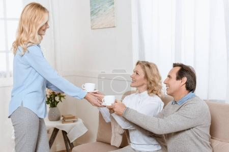 Middle aged man and women having a conversation while drinking tea on sofa