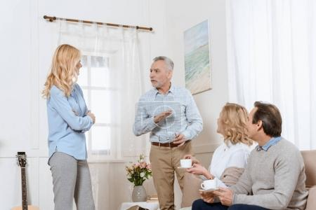 Middle aged men and women having a conversation while drinking tea on sofa