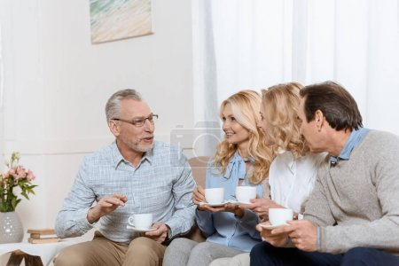 Senior men and women enjoying time together while drinking tea on sofa
