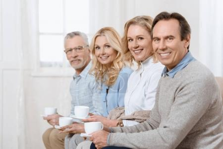 Middle aged men and women having a conversation while drinking tea on sofa looking at camera