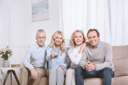 Senior men and women sitting on sofa and watching tv using remote control