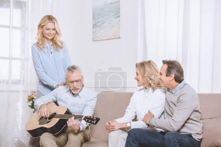 Middle aged men and women listening to guitar music in living room