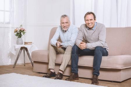 Foto de Dos hombres adultos felizes sentado en el sofá en la sala luz y viendo la televisión - Imagen libre de derechos