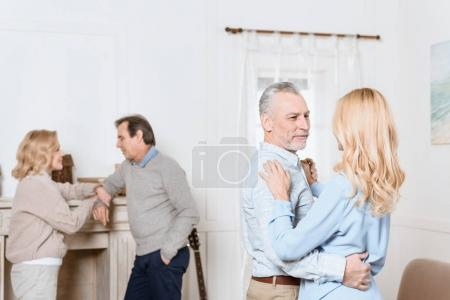 Middle aged men and women dancing by fireplace in cozy room