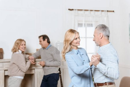 Middle aged men and women dancing and talking by fireplace in cozy room