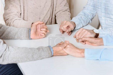 cropped image of friends mily sitting at table and holding hands of each other while praying