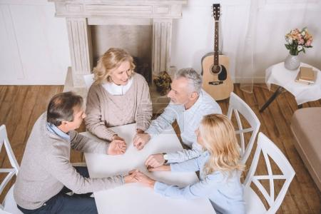 friends sitting at table and holding hands of each other while praying