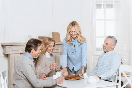woman serving pie on table for sitting friends members