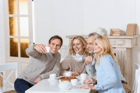 man doing selfie while friends sitting at table with tea and pie