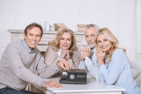 friends sitting at table while using projector on table