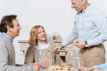 elder man with bottle in hand standing against sitting husband and wife