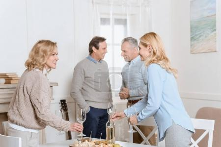 happy friends speaking and drinking beverages while standing against table in room