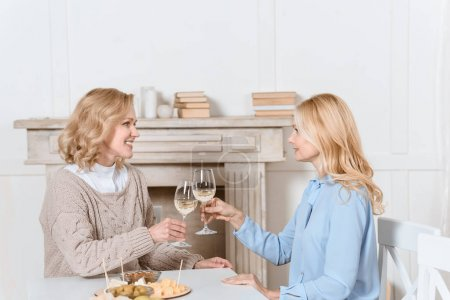 Women cheering with glasses in hands while sitting at table