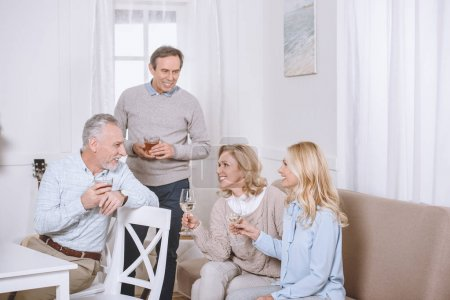 friends sitting on sofa and on chair while speaking in room