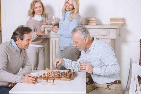 men playing chess while sitting at table, standing woman with glasses on background