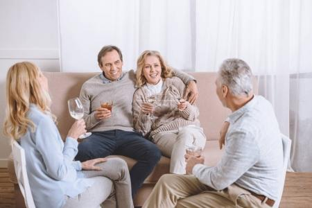 friends with glasses in hands speaking while sitting on sofa in room
