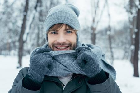 portrait of handsome smiling man looking at camera in winter park