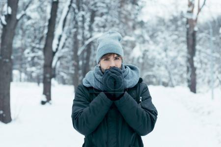 portrait of young man warming hands up while walking in snowy park